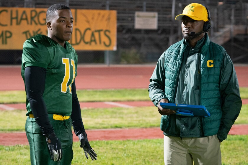 A high school football player stands on the field with his coach, who holds a clipboard.