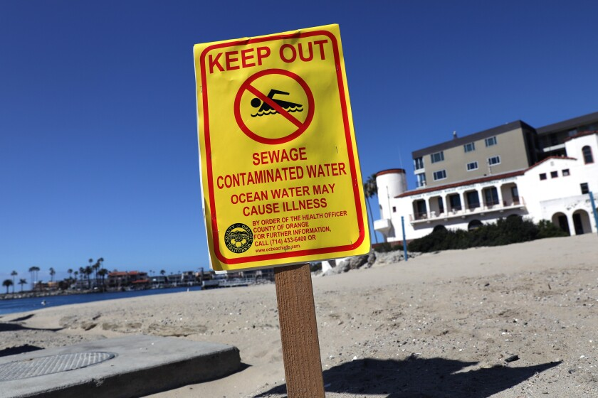 "A sign on a beach says ""Keep Out. Sewage Contaminated Water ...."""
