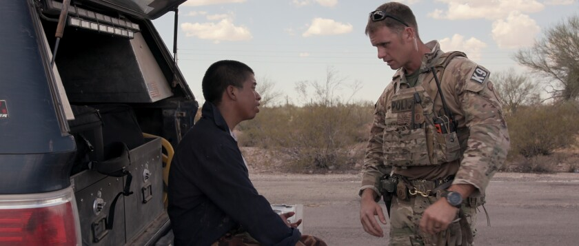 """A migrant, left, seeks help in Tucson's desert in a moment from Netflix's """"Immigration Nation."""""""
