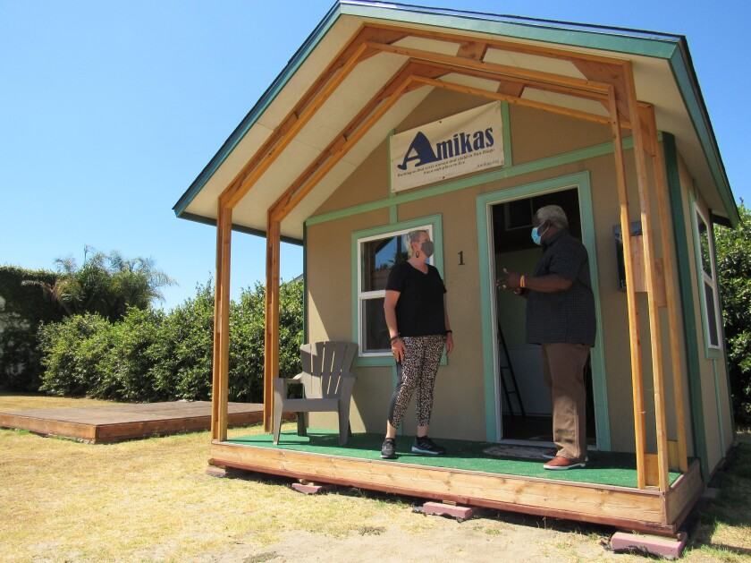 Lisa Kogan and Meridian Baptist Church Pastor Rolland Slade stand outside a demonstration sleeping cabin in El Cajon.