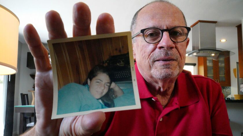 At his home in Oceanside, Tom Dicioccio looks over photos of an old high school friend Marla. Marl