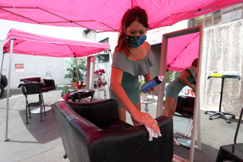 Stylist Regina Muslimova cleans her station after giving a haircut in the parking lot behind her salon in Walnut Creek.