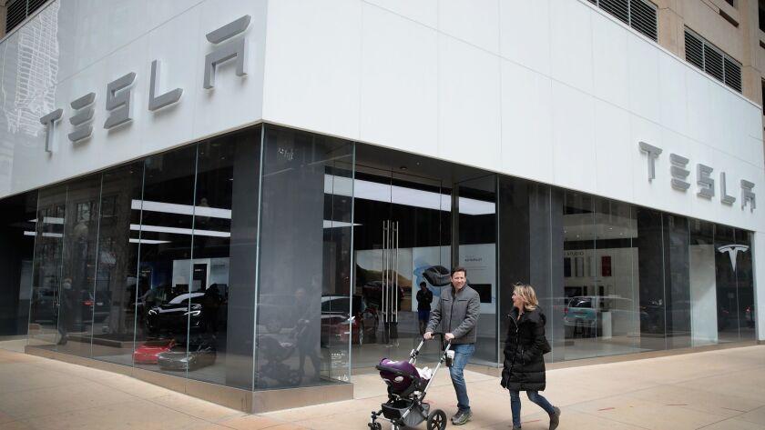 People walk past a Tesla dealership in Chicago.