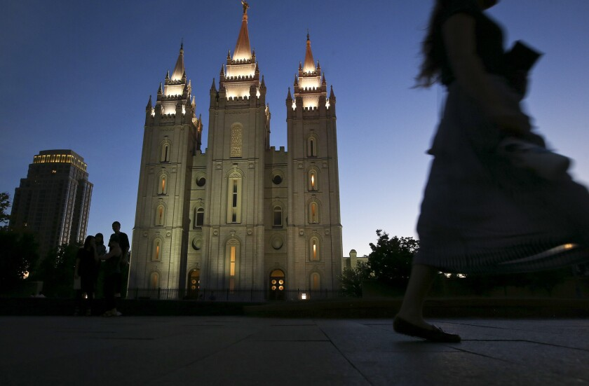 An LDS missionary passes by the Salt Lake Temple at Temple Square in Salt Lake City. Voters this fall in Utah will cast ballots on a measure that would allow medical marijuana.