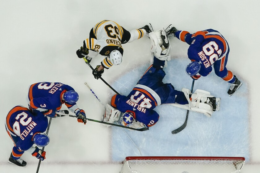 New York Islanders goaltender Semyon Varlamov (40) stops a shot on goal by Boston Bruins' Brad Marchand (63) as teammates Brock Nelson (29), Scott Mayfield (24) and Adam Pelech (3) defend during the first period of Game 4 during an NHL hockey second-round playoff series Saturday, June 5, 2021, in Uniondale, N.Y. (AP Photo/Frank Franklin II)
