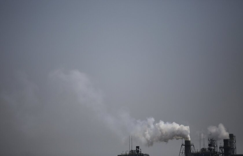 Smoke is discharged from chimneys at a plant in Tokyo, Tuesday, March 25, 2014. Along with the enormous risks global warming poses for humanity are opportunities to improve public health and build a better world, scientists gathered in Yokohama for a climate change conference said Tuesday. (AP Photo/Eugene Hoshiko)