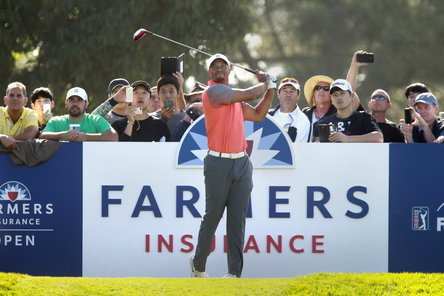 Golf fans watch Tiger Woods' ball sail after he hit from the South Course 18th tee as he and other golfer play in the Pro-Am of the Farmers Insurance Open at Torrey Pines Golf Course in La Jolla on Wednesday, January 22, 2013.
