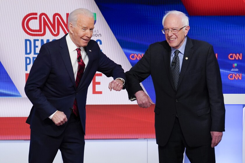 Joe Biden, left, and Bernie Sanders greet each other before a Democratic presidential primary debate March 15 at CNN Studios in Washington on March 15.