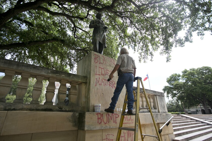 A university worker removes graffiti from a statue of Jefferson Davis on the south mall at the University of Texas in Austin.