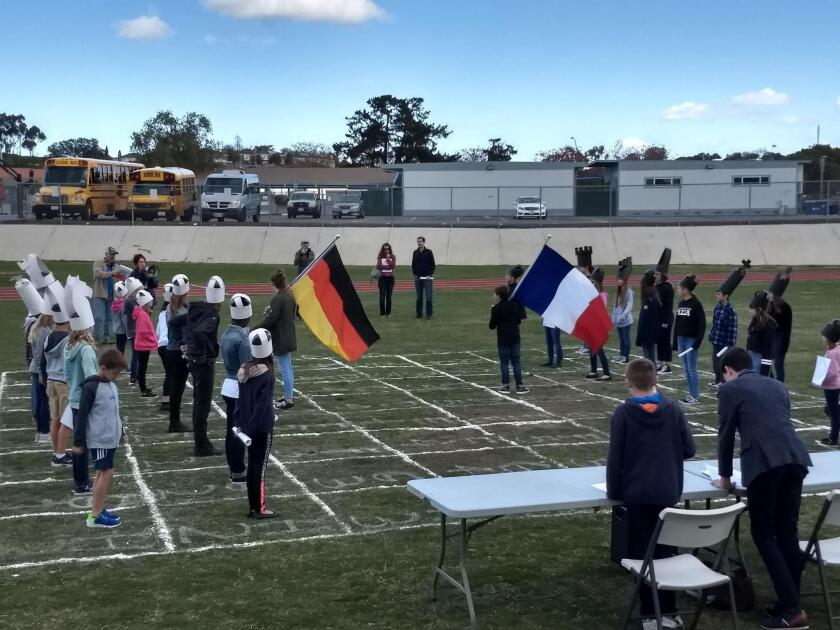 Students work on their conflict film 'Chess Peace,' with a chess board drawn on the sports field of the San Diego French-American School.