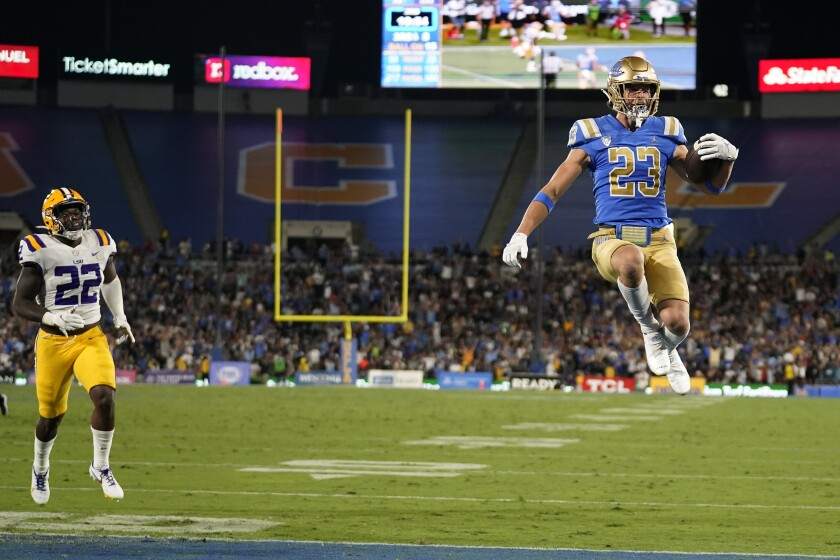 UCLA wide receiver Chase Cota (23) leaps into the end zone for a touchdown after a catch past LSU linebacker Navonteque Strong (22) during the second half of an NCAA college football game Saturday, Sept. 4, 2021, in Pasadena, Calif. (AP Photo/Marcio Jose Sanchez)
