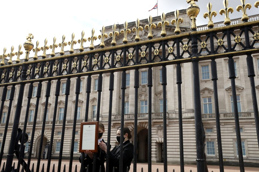 A small placard is affixed to the Buckingham Palace gates