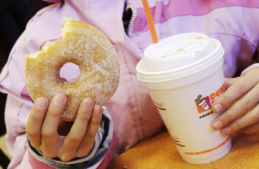 A girl holds a doughnut and a beverage at a Dunkin' Donuts in New York. A Santa Monica location of the doughnut chain is scheduled to open Sept. 2.