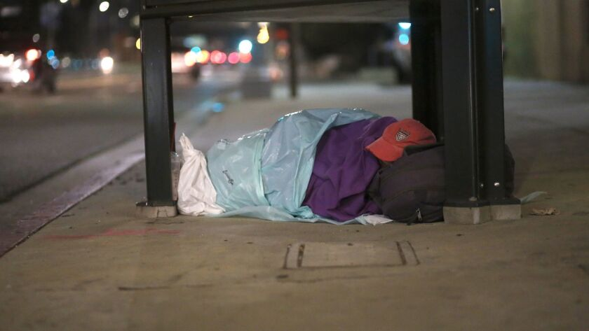 A homeless person sleeps wrapped in plastic bags on Hollywood Boulevard.
