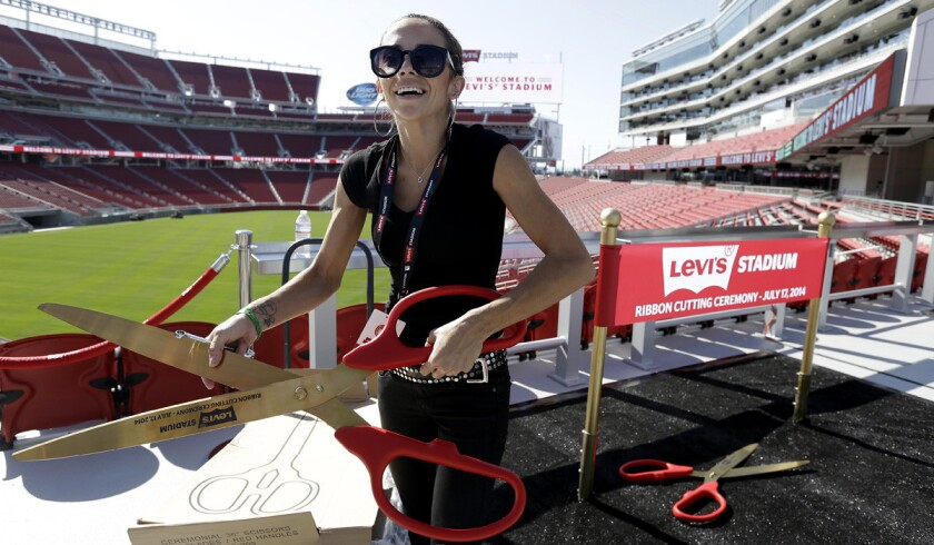 Mahelly Ferreira unpacks a large pair of scissors to be used in a photo booth before the ribbon-cutting ceremony and opening of Levi's Stadium on Thursday.