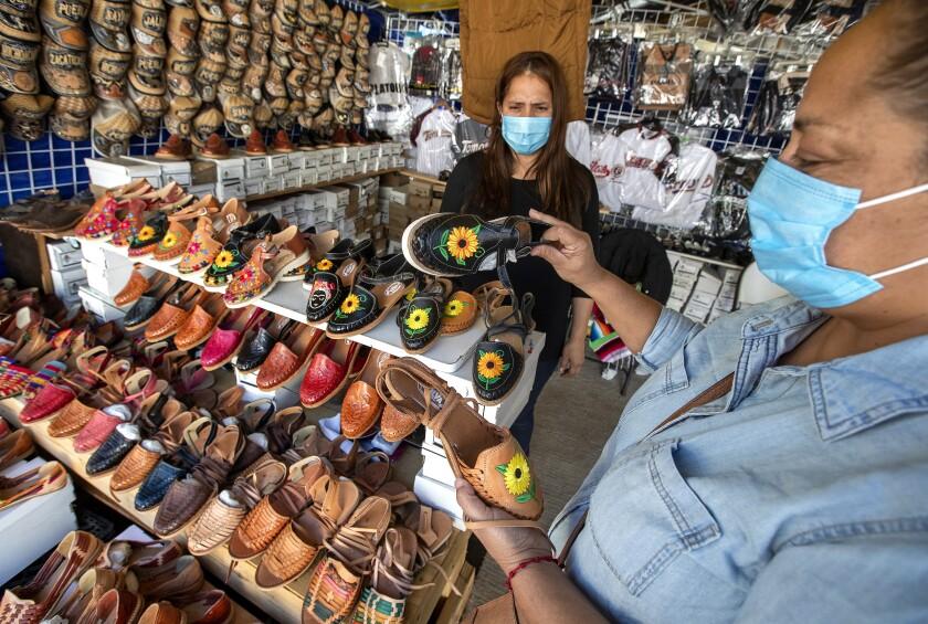 Huarache vendor Maria Silva helps customer Ana Rosa Ornelas of Sacramento.