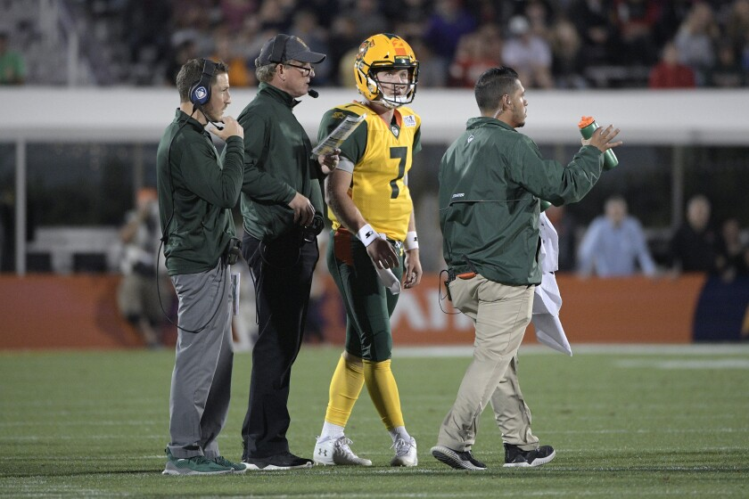 Arizona Hotshots coach Rick Neuheisel, center, talks with quarterback John Wolford.