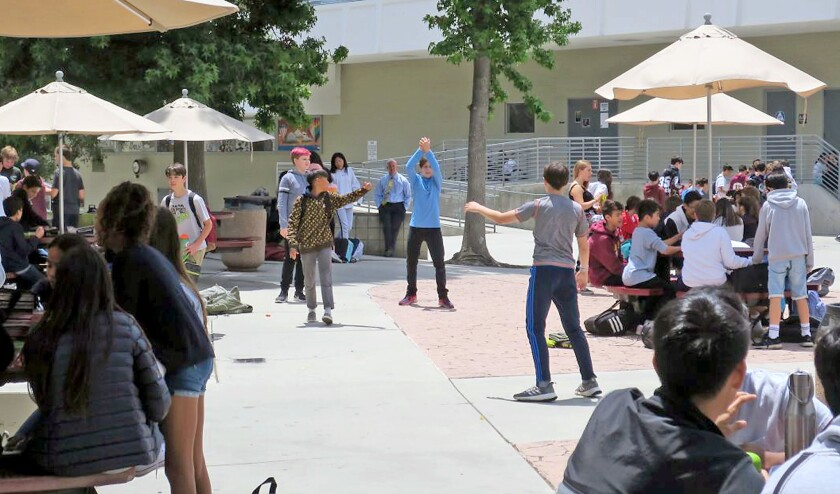 A group of students at La Canada High School 7/8 play catch during a May 21 lunch period, as an alte