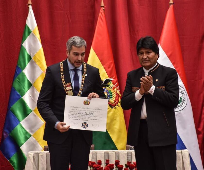 El presidente de Bolivia, Evo Morales (d), condecora a su homólogo paraguayo, Mario Abdo Benítez (i), con el Cóndor de los Andes este sábado, en Oruro (Bolivia). EFE