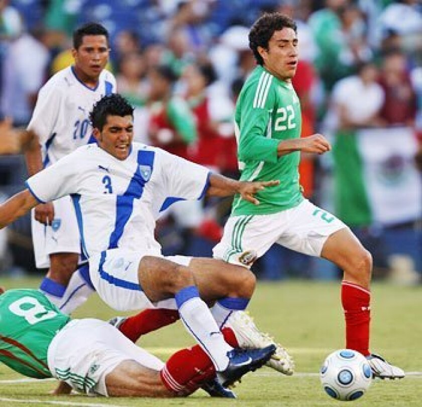 Guatemala's Cristian Noriega (left) is clipped as he and Mexico's Efrain Juarez (22) chase after the ball in the second half of friendly at Qualcomm. El Tri is 17-1-6 against its neighbor to the southeast.   (Sean M. Haffey / Union-Tribune)