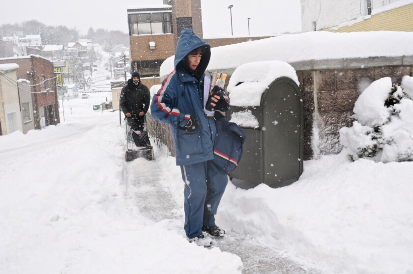 U.S. Postal Service mail carrier Debra Zyk delivers mail on her route in Pottsville, Pa., as Sebastian Lopez clears snow.
