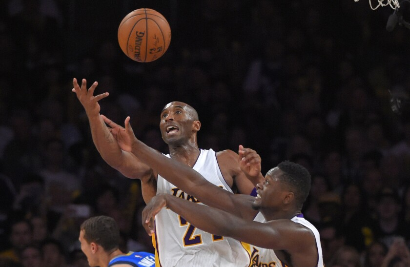 Lakers guard Kobe Bryant, left, and forward Julius Randle go after a rebound during a loss to the Dallas Mavericks.