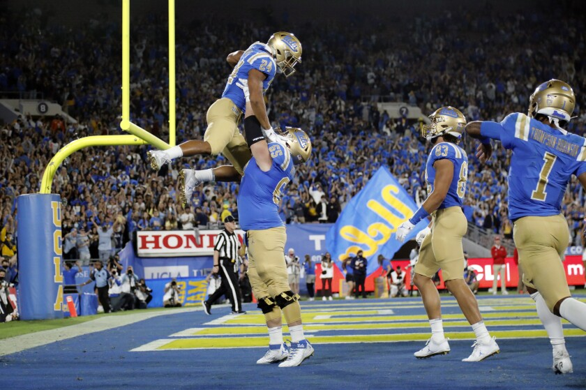 UCLA offensive lineman Paul Grattan lifts up UCLA Bruins running back Zach Charbonnet in the end zone
