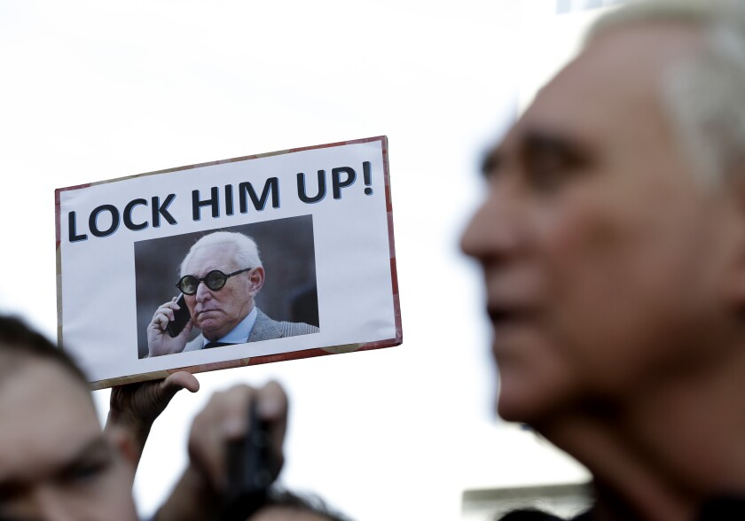 A protester holds up a sign as Roger Stone, right, speaks outside of the federal courthouse in 2019.