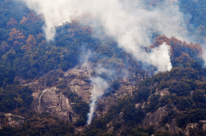 Smoke rises from a tree-filled area adjacent to Moro Rock