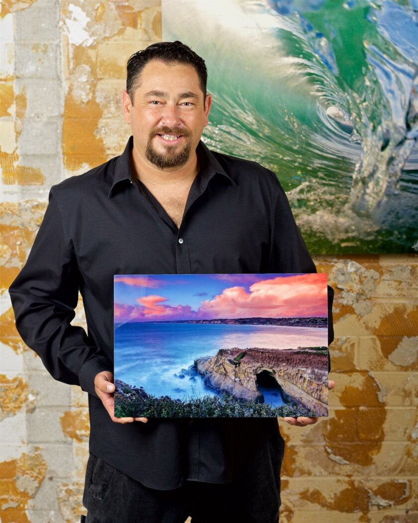 Aaron Goulding holds one of his La Jolla portraits.