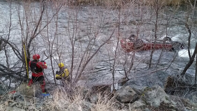 The Siskiyou County sheriff's dive team works to rescue a man trapped in his upside-down car in a frigid river near Yreka, Calif.