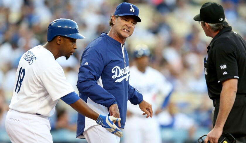 Dodgers Manager Don Mattingly and Chone Figgins (18) argue a batter's interference call with home plate umpire Paul Nauert during the first inning of a game against the Pirates on Friday at Dodger Stadium.