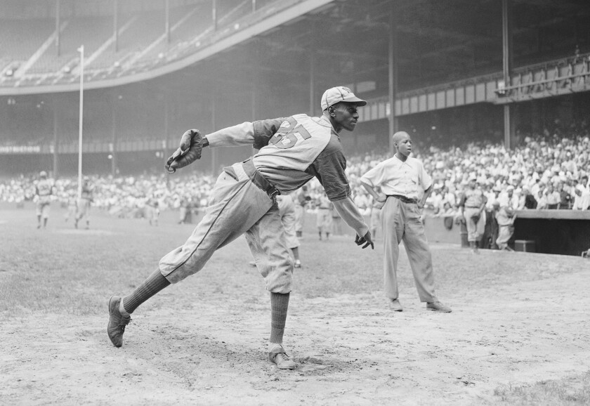 "Kansas City Monarchs pitching great Leroy ""Satchel"" Paige warms up at New York's Yankee Stadium August 2, 1942."