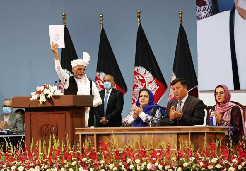 El presidente de Afganistán, Ashraf Ghani, alza una copia de una resolución en el último día de la Loya Jirga, o consejo tradicional afgano, en Kabul, Afganistán, el domingo 9 de agosto de 2020. (AP Foto)