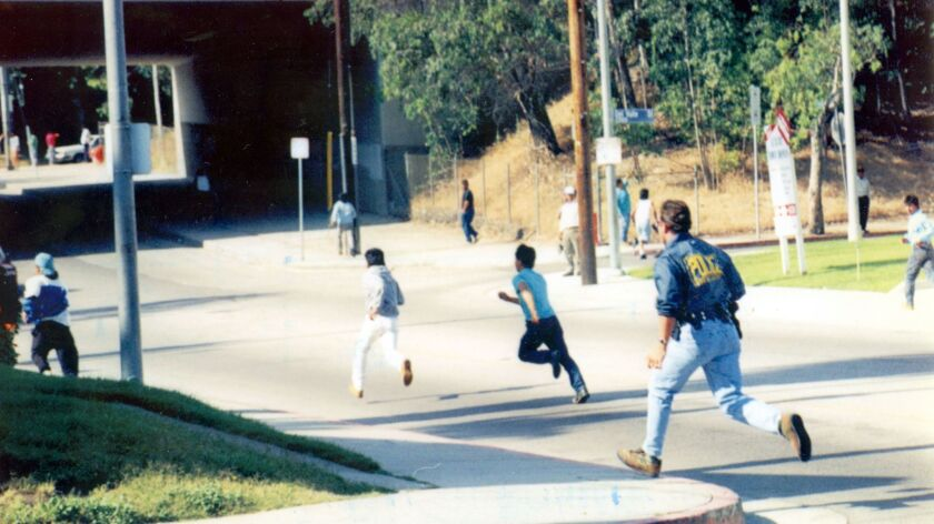 An INS officer chases suspected illegal immigrants during a 1993 raid in Los Angeles.