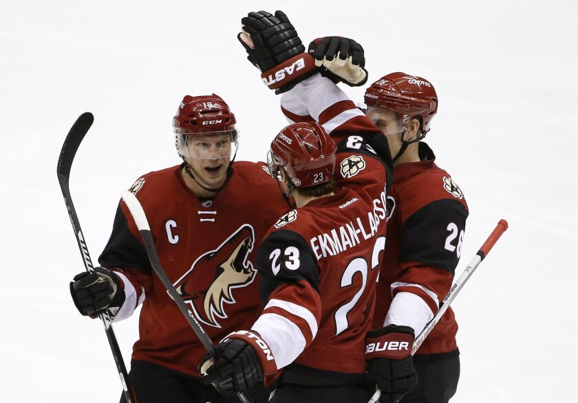 Arizona Coyotes' Oliver Ekman-Larsson (23), of Sweden, celebrates his goal against the Calgary Flames with Shane Doan, left, and Michael Stone, right, during the second period of an NHL hockey game Friday, Feb. 12, 2016, in Glendale, Ariz. (AP Photo/Ross D. Franklin)
