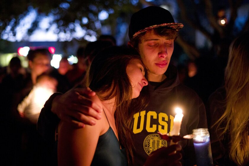 Two students comfort each other during a candlelight vigil held to honor the victims of Friday night's mass shooting on Saturday, May 24, 2014, in Isla Vista, Calif. Sheriff's officials say Elliot Rodger, 22, went on a rampage near the University of California, Santa Barbara, stabbing three people