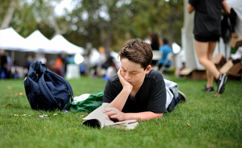 Jasper Joseph, 13, of Santa Monica, dives into a book at the Los Angeles Times Festival of Books at USC on Sunday.