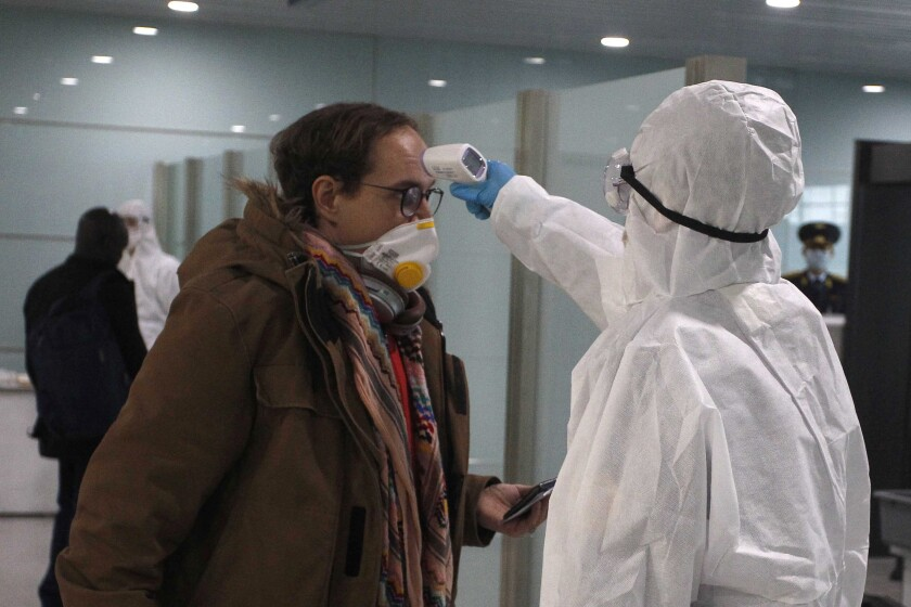 A passenger wearing a mask as a precaution against a new coronavirus has his temperature checked before boarding a flight to Vladivostok, Russia, at the Pyongyang International Airport in Pyongyang, North Korea, Monday, March 9, 2020. (AP Photo/Cha Song Ho)