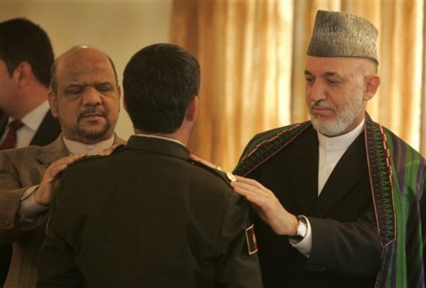 Afghan President Hamid Karzai, right, and first Vice President Muhammad Qasim Fahim, left, participate in a function promoting members of the Afghan security forces at the presidential palace in Kabul, Afghanistan, Saturday, Oct. 2, 2010. Karzai delivered a upbeat and nationalistic speech calling on Afghanistan's police and army to prepare themselves to take charge of protecting and defending the nation after the eventual exit of international forces. (AP Photo/Ahead Massoud)