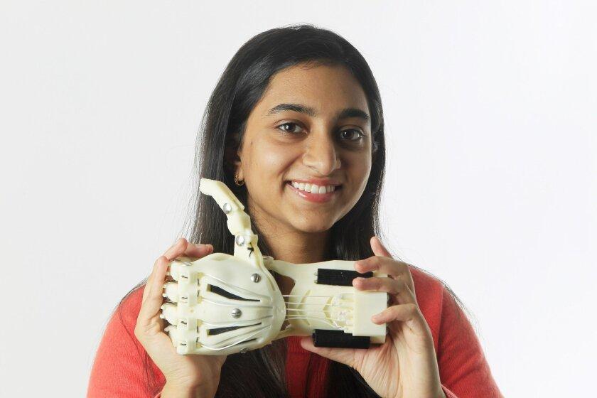 Meghana Reddy holds the prosthetic hand she created on her 3D printer.