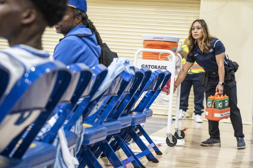 Crenshaw athletic trainer Ellen Kelly grabs towels and water bottles for the basketball players during a timeout at a game Jan. 24, 2020.
