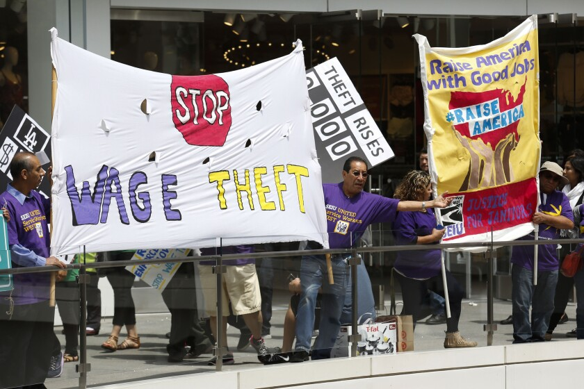 Workers in May hold a rally at the Figat7th shopping center in downtown Los Angeles, supporting anti-wage-theft legislation and a $15-an-hour minimum wage.