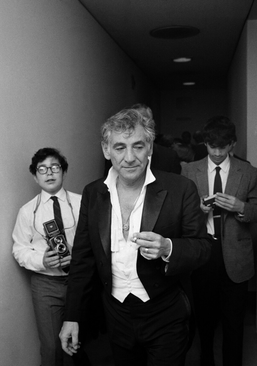 Leonard Bernstein walks to his dressing room following his last performance as music director of the