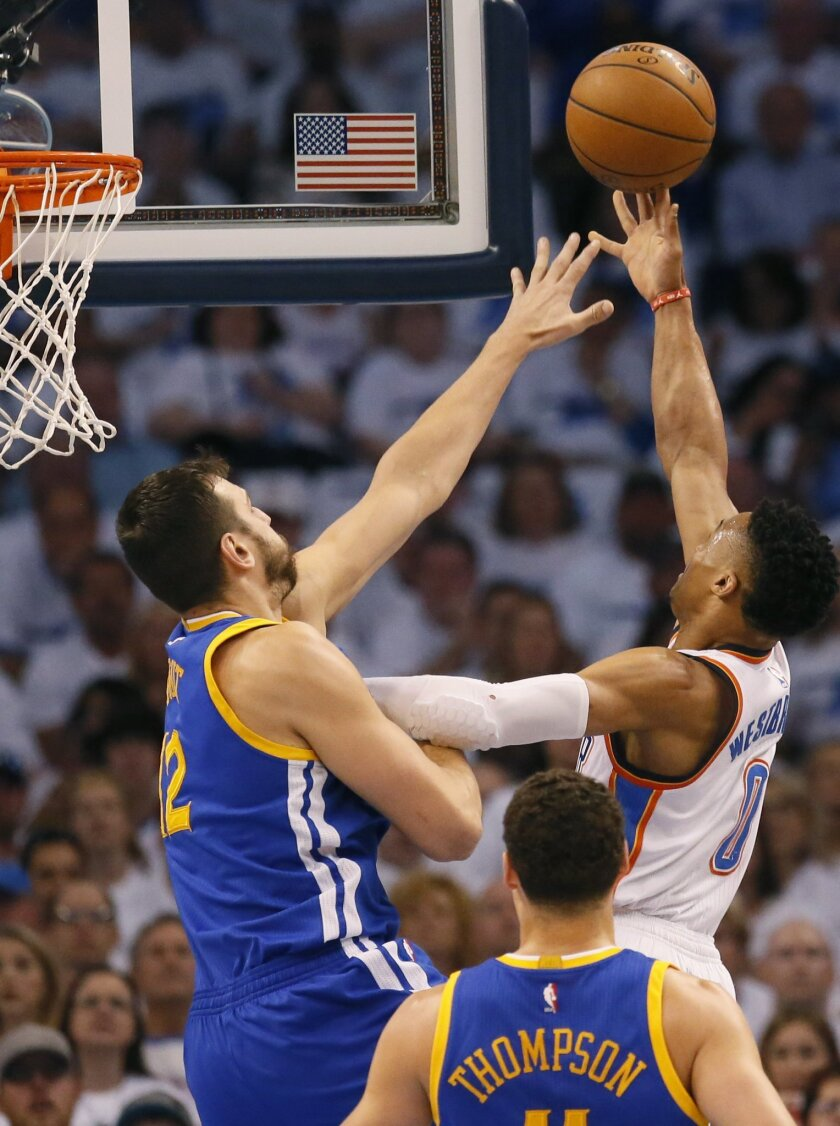 Golden State Warriors center Andrew Bogut (12) defends as Oklahoma City Thunder guard Russell Westbrook (0) shoots during the first quarter in Game 3 of the NBA basketball Western Conference finals  in Oklahoma City, Sunday, May 22, 2016. (AP Photo/Sue Ogrocki)