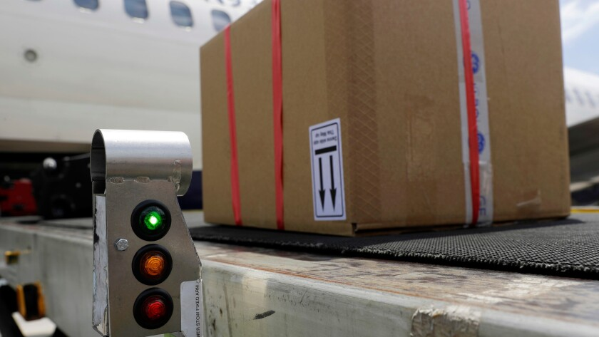 A scanner displays a green light as it detects a tag enabled with radio-frequency identification on a package being loaded onto a Delta flight at Baltimore Washington International Airport.