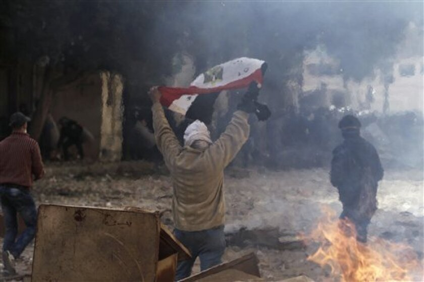 An Egyptian protestor is seen through heat waves from a fire as he raises his national flag during clashes with security forces near the interior ministry in Cairo, Egypt, Friday, Feb. 3, 2012. A volunteer doctor says police and protesters angry over a deadly soccer riot have clashed for the second day in the Egyptian capital, and that one man died in the latest violence. (AP Photo/Muhammed Muheisen)