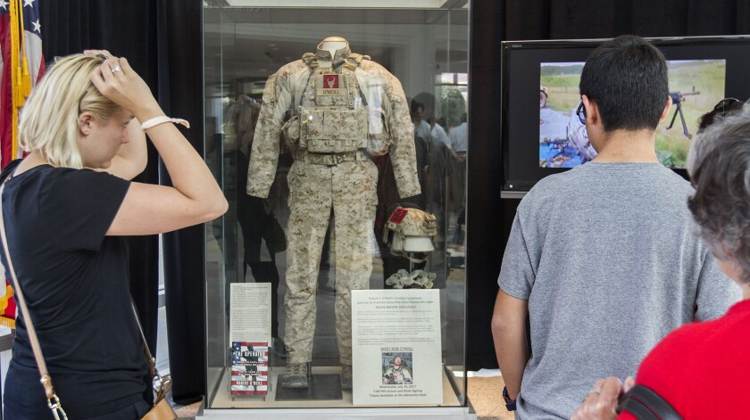 Visitors view the combat fatigues of former Navy SEAL Robert O'Neill, who was part of the mission that killed Osama bin Laden during a 2011 raid in Pakistan. O'Neill's uniform is on display at the Richard Nixon Presidential Library and Museum in Yorba Linda through July 31.