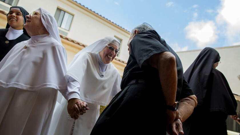 Sister Maria Socorro, center, mingles with priests and fellow nuns after a first vows ceremony.