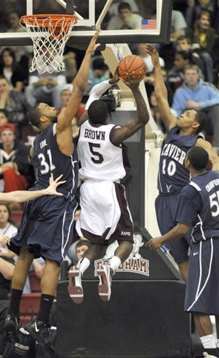 Xavier's Jason Love (31) and Mark Lyons (10) block Fordham's Lance Brown's (5) shot during the first half of an NCAA college basketball game Wednesday, March 3, 2010, in New York. (AP Photo/Kathy Kmonicek)